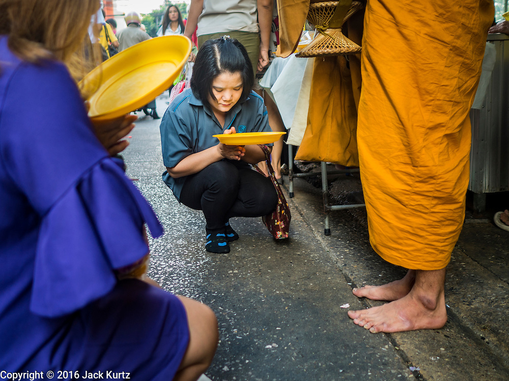 04 JANUARY 2016 - BANGKOK, THAILAND:        A Buddhist monk (standing right) blesses people who made alms offerings to him in Bang Chak Market on the last day it was open. The market closed January 4, 2016. The Bang Chak Market serves the community around Sois 91-97 on Sukhumvit Road in the Bangkok suburbs. About half of the market has been torn down. Bangkok city authorities put up notices in late November that the market would be closed by January 1, 2016 and redevelopment would start shortly after that. Market vendors said condominiums are being built on the land.   PHOTO BY JACK KURTZ