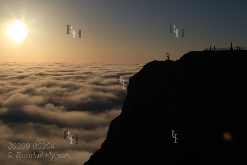 Midnight sun bathes sea of clouds and famous globe atop North Cape cliff near northernmost point in Europe; Mageroya Island, Finnmark, Norway.