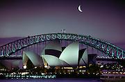 Sydney Opera House and bridge, with quarter moon in Sydney Harbor. Sydney, Australia.