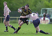 Esher, Surrey. ENGLAND.<br /> <br /> Photo Peter Spurrier<br /> 04/05/2002<br /> Sport - Rugby Union<br /> Tetley's County Championship 1 st Rd<br /> Surrey vs Cornwall<br /> Joe Bearman looking for the gap, is tackled by Surrey's Mark Butterworth.