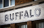 SHOT 10/24/17 10:04:22 AM - Peeling and faded Buffalo signage at Buffalo X-Ray in downtown Buffalo, N.Y. Buffalo, N.Y. is the second most populous city in the state of New York and is located in Western New York on the eastern shores of Lake Erie and at the head of the Niagara River. By 1900, Buffalo was the 8th largest city in the country, and went on to become a major railroad hub, the largest grain-milling center in the country and the home of the largest steel-making operation in the world. The latter part of the 20th Century saw a reversal of fortunes: by the year 1990 the city had fallen back below its 1900 population levels. (Photo by Marc Piscotty / © 2017)