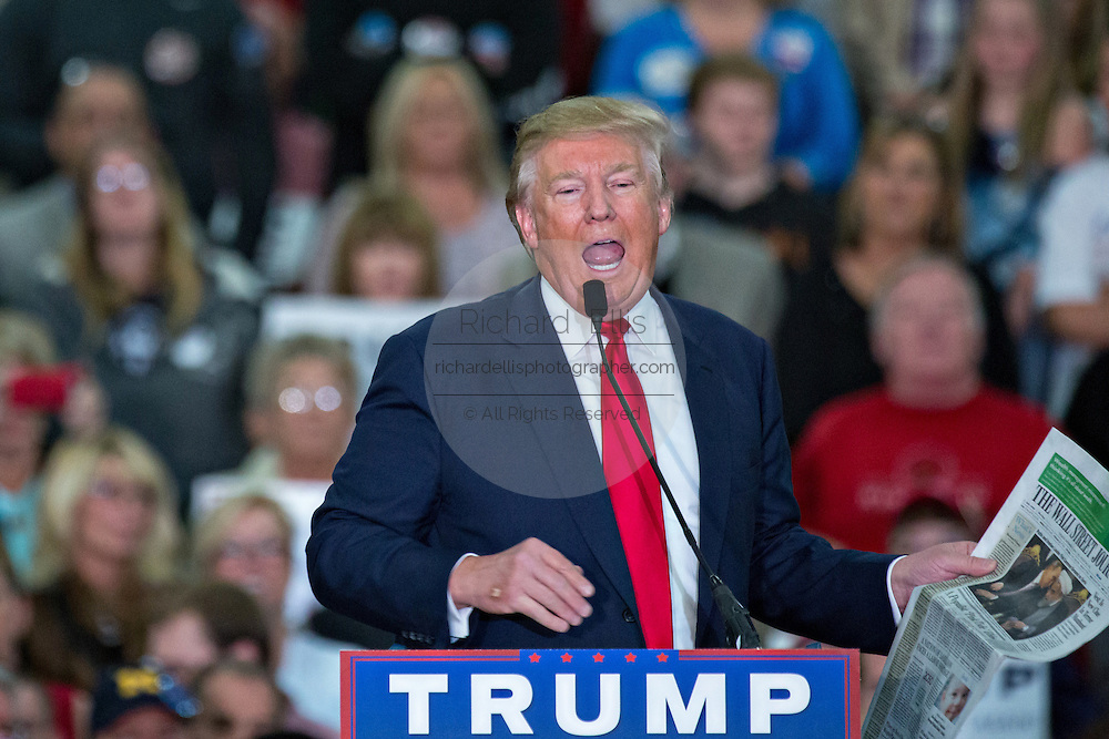 Republican presidential candidate billionaire Donald Trump holds up a copy of the Wall Street Journal as he criticizes the media during a campaign rally at the Myrtle Beach Convention Center November 24, 2015 in Myrtle Beach, South Carolina.
