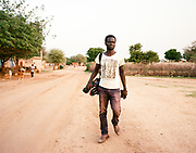 """NUBA MOUNTAINS, SUDAN – JUNE 9, 2018: Filmmaker Yassin Hassan walks through Kouda, the cultural center of Hieban county.<br /> <br /> In 2011, the government of Sudan expelled all humanitarian groups from the country's Nuba Mountains. Since then, the Antonov aircraft has terrorized the Nuba people, dropping more than 4,080 bombs on hospitals, schools, marketplaces and churches. Today, vestiges of the Antonov riddle the landscapes of daily life, where more than 1 million Nuba live in famine conditions – quietly enduring the humanitarian blockade intended to drive them out of the region. The skies are mostly clear. Yet the collective memory of the bombings remains an open wound, and the Antonov itself a persistent threat. So frequent were the attacks that the Nuba nicknamed the high flying aircraft and its dismal hum: """"Gafal-nia ja,"""" they would declare, running to the hillsides. """"The loss of appetite has come."""""""