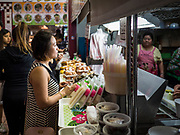 03 AUGUST 2019 - ST. PAUL, MINNESOTA: A woman orders food in the food court at the Hmong Village in St. Paul. Thousands of Hmong people, originally from the mountains of central Laos, settled in the Twin Cities in the late 1970s and early 1980s. Most were refugees displaced by the American war in Southeast Asia. According to the 2010 U.S. Census, there are now 66,000 ethnic Hmong in the Minneapolis-St. Paul area, making it the largest urban Hmong population in the world. There are two large Hmong markers in St. Paul. The Hmongtown Marketplace has are more than 125 shops, 11 restaurants, and a farmers' market in the summer. Hmong Village is newer and has more than 250 shops and 17 restaurants.     PHOTO BY JACK KURTZ