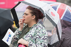 """Trafalgar Square, London, June 12th 2016. Rain greets Londoners and visitors to the capital's Trafalgar Square as the Mayor hosts a Patron's Lunch in celebration of The Queen's 90th birthday. PICTURED: A woman with an """"I love London"""" umbrella watches the performers on stage."""