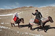 The best man takes a picture of the bride. After a two-day horse journey, Ikhbal will soon arrive at her husband's camp, near the China border, escorted by the groom's best man. The majority of women have never been more than a few miles from where they were born. This is Ikhbal's biggest journey..With Ikhbal, the recently married woman  moving for the first time to her husband's camp..