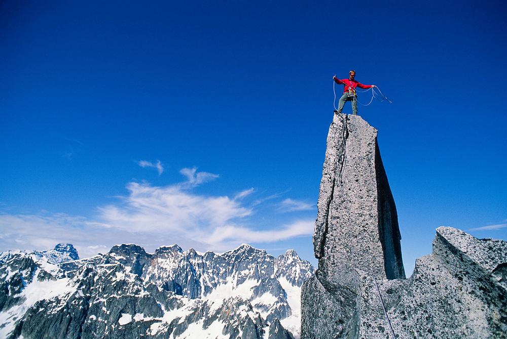 Alaska. Little Switzerland.  Single climber, John Mattson, coiling rope on top of a granite spire.