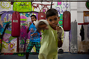 Children, young men training at Boxing school Instituto Todos Na Luta Everyone in the struggle institute, set up by Raff Giglio in Vidigal. Since pacification in 2011, Vidigal has slowly become known as what some call a model favela, seen as the safest favela in Rio, home to a mixed community which now includes foreigners, hostels, restaurants, theatres and creative businesses.