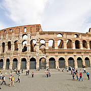 ROME, Italy - A wide-angle shot of Rome's famous and historic Coliseum during the daytime, with tourists around the piazza.