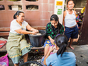 06 FEBRUARY 2015 - BANGKOK, THAILAND: A Buddhist family peels garlic in front of their home in the Santa Cruz Catholic neighborhood in Thonburi, Bangkok. The neighborhood around the church is known for the Thai adaptation of Portuguese cakes baked in the neighborhood. Several hundred Siamese (Thai) Buddhists converted to Catholicism in the 1770s. Some of the families started baking the cakes. When the Siamese Empire in Ayutthaya was sacked by the Burmese, the Portuguese and Thai Catholics fled to Thonburi, in what is now Bangkok. The Portuguese established a Catholic church near the new Siamese capital. There are still a large number of Thai Catholics living in the neighborhood around the church.       PHOTO BY JACK KURTZ