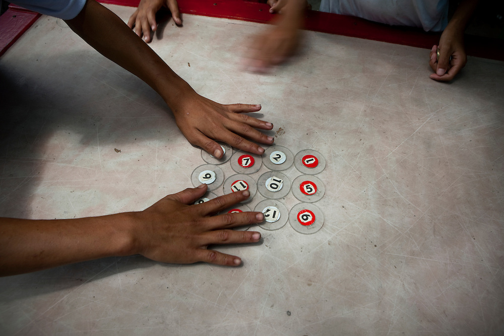 MANILA, PHILIPPINES: Teenagers play pool on the streets of San Fernando, in Philippines. <br /> In tagalog language, billiards and pool are different games. Instead of using marble balls, pool is played with 'pitchas', and to make the table slippery, they pour powder on it. The table is different from the billiard table; this game is played on a squared table with only four pockets, one in every corner.