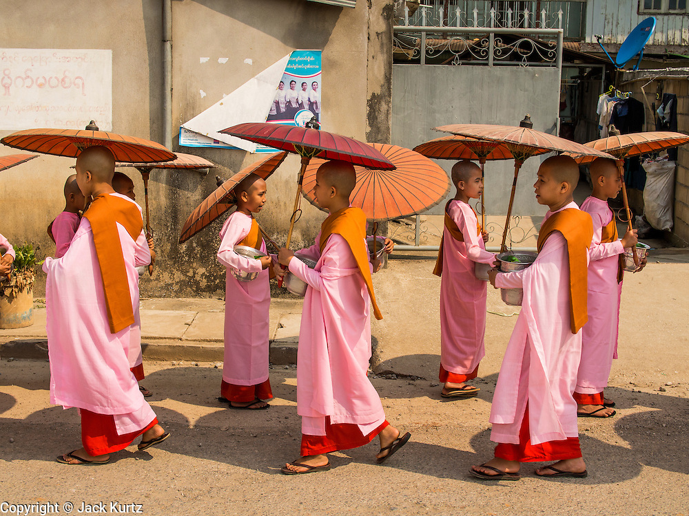 "26 APRIL 2014 - TACHILEIK, SHAN STATE, MYANMAR: Buddhist  nuns go out on their alms rounds in the morning in Tachileik, Shan State, Myanmar (Burma). There are about 75,000 Burmese women living as nuns, sometimes called ""Bhikkhuni"" although the term has fallen out of favor since Bhikkhuni are no longer ordained. Many of the women who become nuns do so to escape poverty or abuse.   PHOTO BY JACK KURTZ"