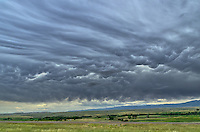 Mammatus clouds are a cellular pattern of pouches that hang beneath a much larger cloud. The formation isn't very distinct here as the wind breaks it up. This stormy scene occurred over the Bighorn Mountains in northeast Wyoming.<br />