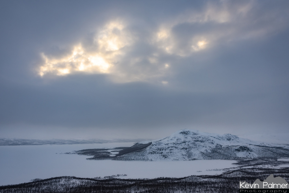 In the far northwest corner of Finland is the tiny village of Kilpisjärvi. This is the only part of the country that touches the Scandinavian Mountains, and it's near Finland's highest point. The elevation and close proximity to the Arctic Ocean makes this the snowiest place in the country, and the snow here had a different quality than any other I've seen. It was so light and fluffy it could be blown off the windshield with my breath, and footprints in the deep snow pack left behind aqua-blue holes. I climbed halfway up one of the mountains, Saana, to obtain this view as the sun struggled to emerge. On the other side of the frozen lake is Sweden, with Norway to the right. This far above the Arctic Circle, trees can not grow above 600m. After this I tried climbing higher, but the route became icy, and visibility was nearing whiteout  so I was forced to turn back.