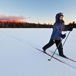 A girl cross-country skiing on Little Lyford Pond in the Maine Woods.