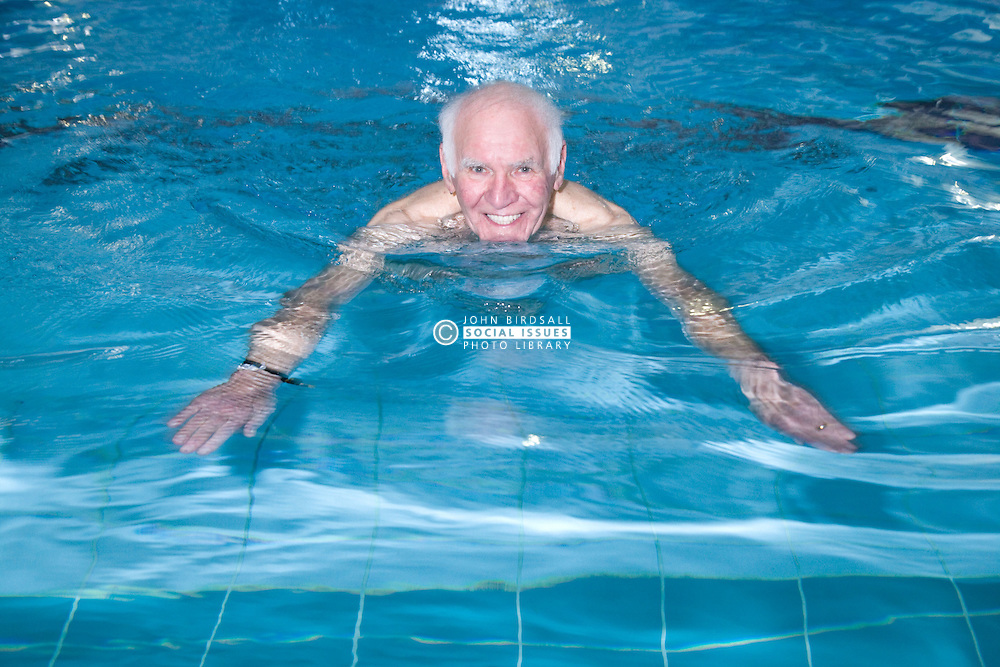 Older man swimming in the pool at his local leisure centre,