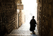 An orthodox woman walks toward a bright street in old city Jerusalem passing next to one of the many police stations there to guarantee security to a city at constant risk of troubles.