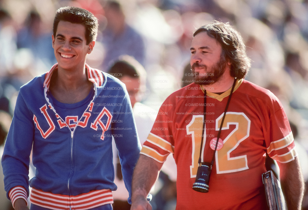 EDMONTON, CANADA - OCTOBER 11:  Actor Robby Benson #722 of the USA (left) plays the role of Billy Mills in the movie Running Brave directed by Donald Shebib (right) filmed in Commonwealth Stadium in Edmonton, Canada in this photograph taken October 11, 1982 during production of the film.  The movie recreates Billy Mills' historic win in the 1964 Olympic Games 10000 meter race.  (Photo by David Madison/Getty Images)