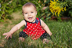 Baby Girl Sitting on Grass Smiling