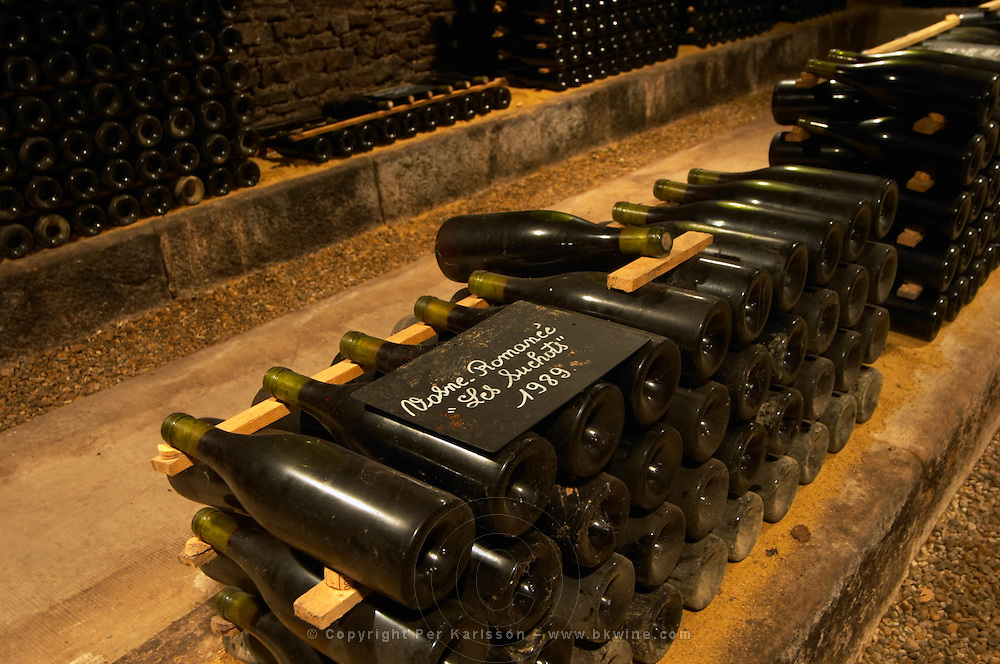In the underground wine cellar: a pile of bottles of Vosne Romanee Romanée Les Suchots 1989 red Burgundy wine with the appellation written in white text on a black chalkboard chalk board on a gravelly pebbly soil, Maison Louis Jadot, Beaune Côte Cote d Or Bourgogne Burgundy Burgundian France French Europe European