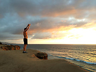 Man stretching on cliffs overlooking the ocean at Del Mar, CA before run.