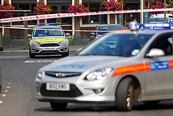 © Licensed to London News Pictures. 07/08/2016. London, UK. Police officers investigate a crime scene as a 16-year-old boy is fighting for life in hospital after he was shot on Lea Bridge Road, near Bromley Road in Leyton, London on 7 August 2016. Photo credit: Tolga Akmen/LNP