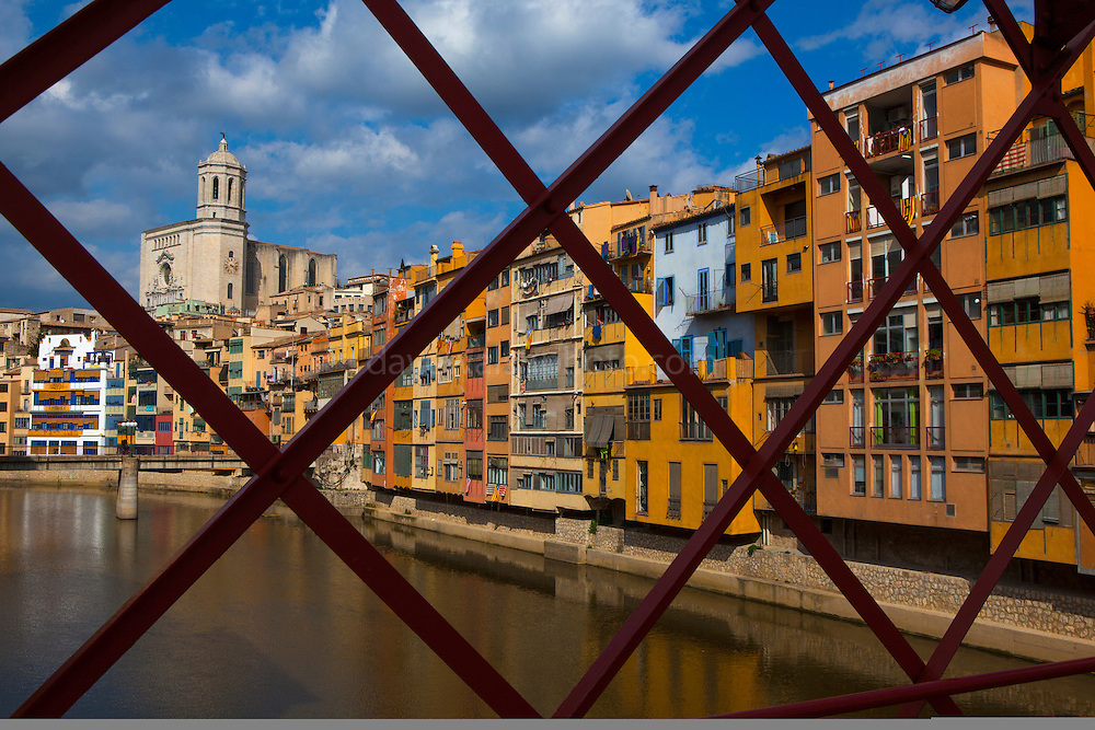 Colourful buildings seen through the Palanques Vermelles bridge  over the river Onyar, in Girona, Catalonia, Spain