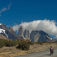 Tourists on motorcycles pass guanacos grazing below the Mount Almirante Nieto and the Towers of Paine in Torres del Paine National Park, Chile.