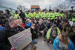 © Licensed to London News Pictures . 17/03/2014 . Barton Moss , Salford , UK . Protesters , including Bez , sit in the road , blocking the lorries' path . Happy Mondays dancer , Bez ( Mark Berry ) , joins protesters at the Barton Moss anti-fracking protest site in Salford today (Monday 17th March 2014) . Bez has said he will stand for MP in the constituency of Salford and Eccles in 2015 . Photo credit : Joel Goodman/LNP