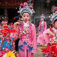 Children, dressed like Chinese opera performers and adorned with necklaces of money, wait for the procession of the Wenxing Mazu from the temple.  <br /> <br /> Although Mazu is classified as a Chinese popular or folk religion, because of the inherent pluralism of Chinese religion, her worship may also be intermixed with Buddhist or Taoist beliefs. For example, in this philosophical understanding of religion, belief in the Buddha does not exclude belief in other deities, and visa versa. There is no conversion, therefore the belief in one god or religion does not require rejection of another god or religion. As evidence of this, there are many Mazu temples that are officially registered with the government as Taoist or Buddhist temples.