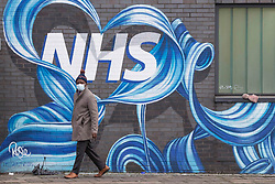 © Licensed to London News Pictures.15/01/2021, London, UK. A member of the public walks past the mural made by <br /> Rosie Woods in east London as the Covid-19 death toll in the UK rose by 1,248 yesterday, the third highest daily increase during the pandemic. Photo credit: Marcin Nowak/LNP