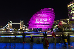 © Licensed to London News Pictures. 04/062016. LONDON, UK.  Tourists look at City Hall next to Tower Bridge as it is illuminated in hot pink, with a '5 May' calendar projection to mark the London Mayoral and local elections taking place on 5th May and remind Londoners to visit their polling stations and vote. City Hall is one of a number of landmarks across London that are being illuminated in hot pink this evening.  Photo credit: Vickie Flores/LNP