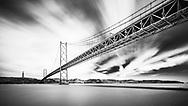 Monochrome long exposure image of Ponte 25 de Abril spanning the Tagus River estuary in Lisbon, Portugal