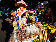 19 NOVEMBER 2014 - BANGKOK, THAILAND:  A vendor in Khlong Toei Market in Bangkok. Between July and September the economy expanded 0.6 percent compared to the previous year, the National Economic and Social Development Board (NESDB) reported. Thailand's economy achieved a weak 0.2 per cent growth across the first nine months of the year. The NESDB said the Thai economy is expected to grow by 1 percent in 2014. Authorities say the sluggish growth is because tourists have not returned to Thailand in the wake of the coup in May, 2014, and that reduced demand for computer components, specifically hard drives, was also hurting the economy. Thailand is the leading manufacturer of computer hard drives in the world. The Thai government has announced a stimulus package worth $11 billion (US) to provide cash handouts to farmers and promised to speed up budget spending to boost consumption.   PHOTO BY JACK KURTZ