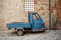 Photo of a little blue truck resting on the streets of San Quirico d'Orcia, Italy.