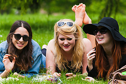 London, May 17th 2014. Three students, Saphia, Billie and Bethan [checked,correct] take a break from their studies to enjoy the warm weather in Regent's park as London basks in the warmest weather so far this year.