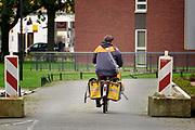 Nederland, the netherlands, Nijmegen, 8-10-2020  Een vrouwelijke postbode bezorgt de post op de fiets rijdt in de stad . De Postfiets, postbike, moet wel zelf betaald worden .Foto: ANP/ Hollandse Hoogte/ Flip Franssen