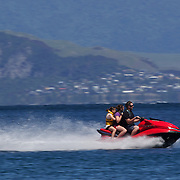 A man and two girls riding on a jet ski on the water at Lake Taupo. Taupo, New Zealand,, 8th January 2011. Photo Tim Clayton