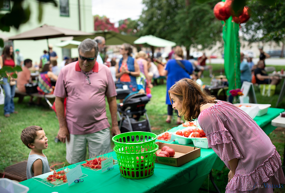 The Greensboro Farmers Curb Market (501 Yanceyville Street) held its Annual BLT Challenge and Tomato Celebration Day on Saturday, August 11th from 9 am – noon on the lawn at the corner of Lindsay & Yanceyville St. The Battle of the BLT was held to name the Best Market BLT for 2018.<br /> Teams of local restaurants and food enthusiasts created their best BLT. Customers had the opportunity to sample all sandwiches and vote for their favorite BLT.  The winner was announced at the end of market, with the title of Best BLT.<br /> Greensboro's best chefs, restaurants and food enthusiasts compete for this title annually. Melt Kitchen & Bar, 2017's winner, will be back to the challenge and up against Reto's Kitchen and a Greensboro Farmers Market team led by Chef Steve Terrill of Red Chair Dinners.<br /> BLT Challenge plates will be available for a minimum donation of $6 per plate, while supplies last.  Each plate will consist of a ¼ sandwich/slider size from each competitor, a side of Mt.Olive pickles, and a ballot to cast for the best BLT sandwich. Payment options include cash and credit.<br /> Additionally, customers will be able to sample up to twenty different varieties of tomatoes that will be in season and available for purchase at the Market. Better Boy, German Johnson, Pink Girls, Sun Gold, Cherokee Purple, Husky Cherry, Juliet, and Plum tomatoes are just a few of the popular varieties that are grown by local vendors and currently in season.<br /> Customers will be able to enjoy live music by a local artist and kid friend activities on the lawn. Picnic table seating is provided, and patrons are encouraged to bring picnic blankets. Laura Jane Vincent, a performer, multi-instrumentalist, and singer-songwriter, performed live indie folk music from 9 am – noon on the lawn.<br /> The Annual BLT Challenge & Tomato Celebration Day is part of the fundraising efforts of Greensboro Farmers Market, Inc., a non-profit organization. Any proceeds benefit GFM, Inc. and defer vend