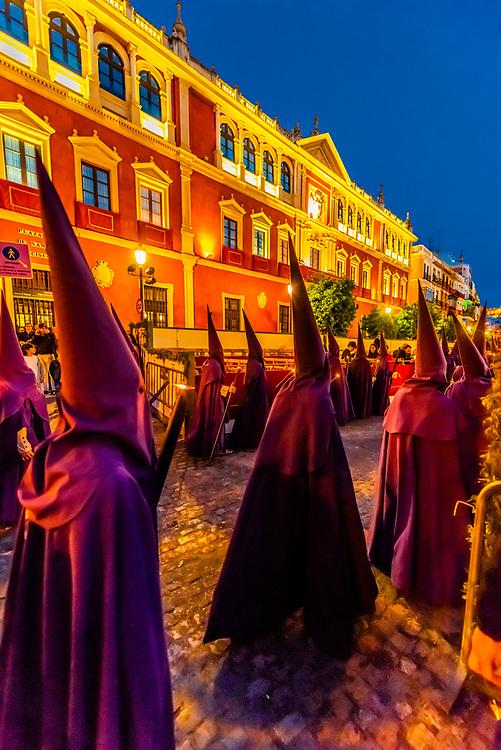 Hooded Penitents (Nazarenos) in the procession of the Brotherhood (Hermandad) La Quinta Angustia, Holy Week (Semana Santa), Seville, Andalusia, Spain.