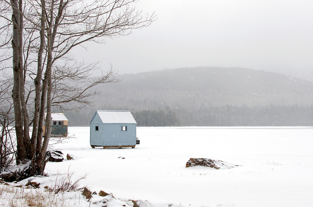 Ice fishing huts during a snowstorm in Acadia National Park, with Cadillac Mountain in the distance.