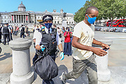"A Police officer (L) carries the possesions of photojournalist Craig Bernard (R) in Trafalgar Square, central London on Sunday, Aug 9, 2020 - after they asked him to be sitting in their van and was going to be questioned in Holborn Police station. Bernard was covering a demonstrative action of the environmental activists' group Extinction Rebellion. A Police officer told a member of ""Legal Observers"" in the scene that among the reason why he was arrested for allegedly committing a quote: ""Affray"" and riding an uninsured e-scooter. (VXP Photo/ Vudi Xhymshiti)"