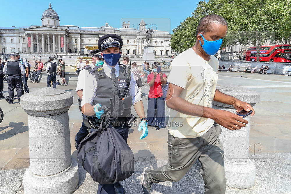 """A Police officer (L) carries the possesions of photojournalist Craig Bernard (R) in Trafalgar Square, central London on Sunday, Aug 9, 2020 - after they asked him to be sitting in their van and was going to be questioned in Holborn Police station. Bernard was covering a demonstrative action of the environmental activists' group Extinction Rebellion. A Police officer told a member of """"Legal Observers"""" in the scene that among the reason why he was arrested for allegedly committing a quote: """"Affray"""" and riding an uninsured e-scooter. (VXP Photo/ Vudi Xhymshiti)"""