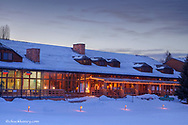 Grouse Mountain Lodge at winter dusk with lit cross country ski course in Whitefish, Montana, USA