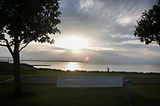 The sun sets by the sea in Borstahusen near Landskrona, Sweden, 22nd of August 2016. A white picket fence throws shadows while a couple walk by in the setting sun light.