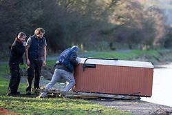 © Licensed to London News Pictures. 29/12/2015. Elland UK. A group of men retrieve a hot tub that has been left stranded on the banks of the Calder & Hebble Navigation at Park Nook Lock in Elland after recent flooding.  Photo credit: Andrew McCaren/LNP