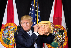 November 7, 2016 - Florida, U.S. - DONALD TRUMP takes a break from speaking to compare his face to a mask during a rally at the Sarasota Fairgrounds. Trump spotted the mask in the crowd, and had it passed up to him. America goes to the polls on Tuesday, Nov. 8. (Credit Image: © Loren Elliott/Tampa Bay Times via ZUMA Wire)