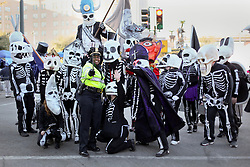 09 February 2016. New Orleans, Louisiana.<br /> Mardi Gras Day. Walking with Skeletons. Stopping at Lee Circle for a selfie with a police officer from NOPD. The Skeleton Krewe meet before sunrise and walk 5 miles from Uptown, making their way along St Charles Avenue and into the French Quarter where they celebrate Mardi Gras Day.<br /> Photo©; Charlie Varley/varleypix.com