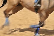 Close up side view of the feet of a running horse