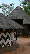 Traditional mud and thatched roof homes sit in front of a communications tower, representing the dichotomy of modern day Africa in Victoria Falls Town, Hwange District of Matabeleland, North Province of Zimbabwe.